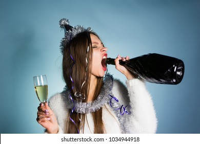 drunk woman drinks champagne from a bottle