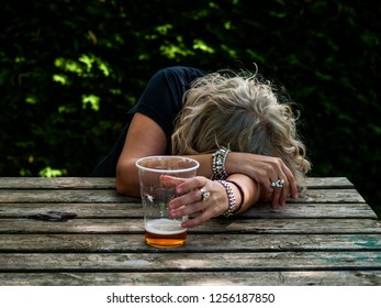 A drunk woman with a glass of beer in her hand, unconscious, leaning on a table