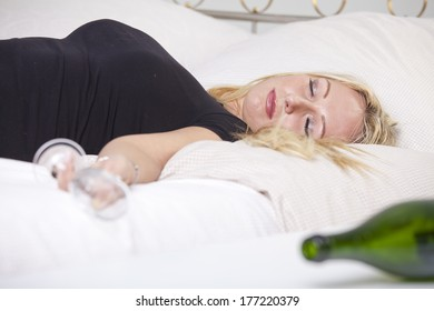 Drunk woman with glass, sleeping on bed