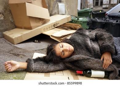 drunk woman lying in trash with bottle of wine