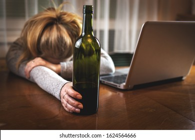 Drunk woman with open laptop sleeping on table after drinking alcohol. Red wine bottle in female hand. Insomnia problem