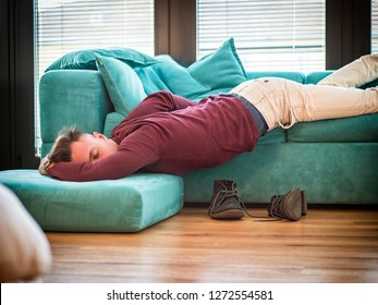 Drunk Young Handsome Man Resting on Couch in the Living Room with Head on the Floor.