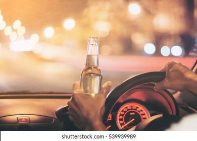 """Un joven ebrio conduce un camión con una botella de cerveza.  Esta es una foto de la campaña """"No bebas para conducir"""". Enfoque selectivo"""