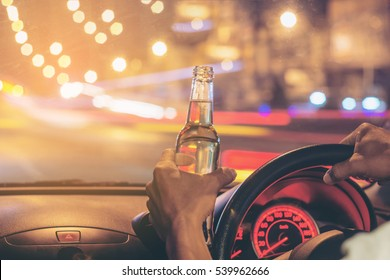 "Drunk young man drives a car with a bottle of beer.  This is a campaign picture of ""Don't Drink for Drive."""