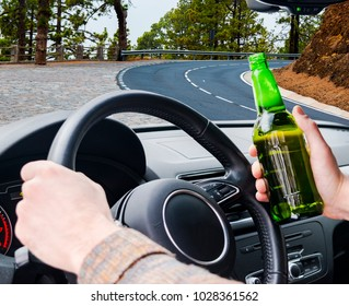 Drunk young man driving a car on the road with a bottle of beer. Don't Drink and drive. Drunk driving under the influence. Driving while intoxicated. Dangerous drunk driving concept.
