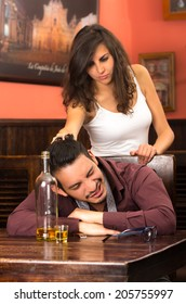 drunk young man sleeping and angry girlfriend in a bar pulling his hair