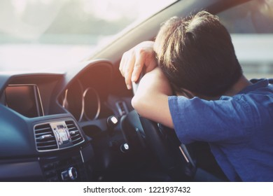Drunk young man slumped on steering wheel be tired sleep in car driving. concept sleepy while driving travel, do not drive. It can be dangerous.