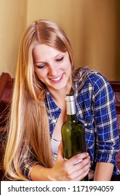 Drunk young woman with bottle of alcohol.