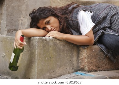 drunk young woman holding bottle of wine lying on stone stairs