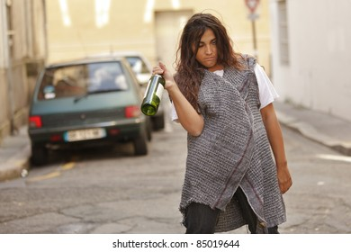 drunk young woman holding bottle of wine walking in city street