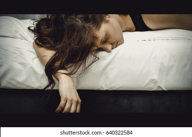 Drunk young woman sleeping on bed.