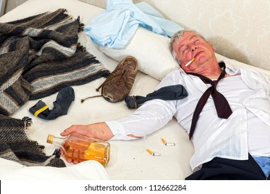 Drunken alcoholic sleeping in a messy bed