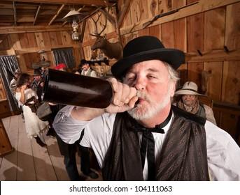 Drunken man chugs a bottle of alcohol in a saloon