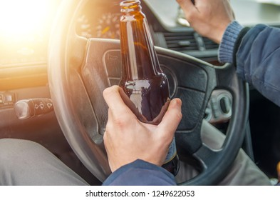 A drunken man driving a car with a bottle of alcohol in his hand.A man holds a driving wheel and a bottle of beer.