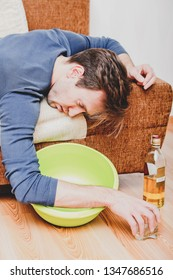 Drunken man is sleeping on sofa with bowl under bed. Acohol addiction.