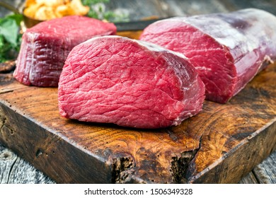 Dry aged beef fillet steak natural as closeup with chanterelles on a wooden cutting board