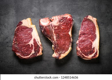 Dry aged beef steaks - ribeye, striploin, t-bone steaks on Black slate background. Top view with copy space.