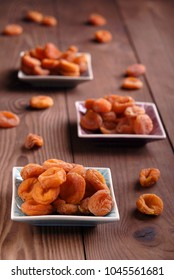 Dry apricots on a plate on a brown wooden background.