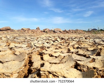 dry arid cracked ground with big rocks in blue sky white clouds