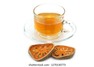 Dry bael fruit with slices and bael juice in glass on white background.