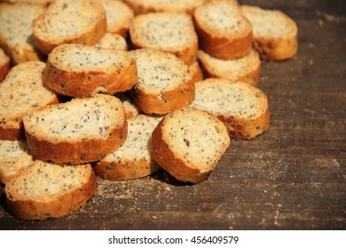 Dry bakery products with wholegrain flour with poppy seeds on wooden background, bread, crackers