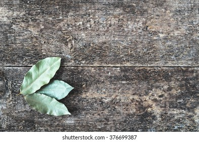 Dry bay leaf on the wooden rustic background, top view. Bay leaf background.  Daylight.