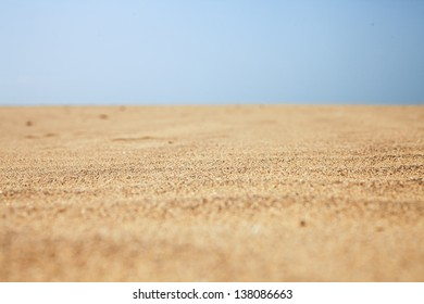Dry beach sand and clear blue sky close-up