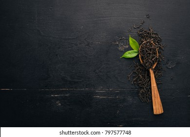 Dry black tea. On a wooden background. Top view. Copy space.