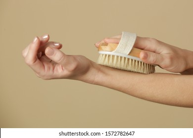 Dry body brush, Woman dry brushing body to reduce cellulite, detoxify the lymphatic system, and achieve beautiful smooth skin. Dry skin brushing as part of morning health and energy routine.