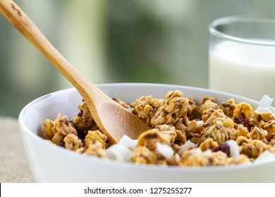 Dry breakfast cereals. Crunchy honey granola bowl with flax seeds, cranberries, coconut and a glass of milk close up. Healthy, clean and fiber food