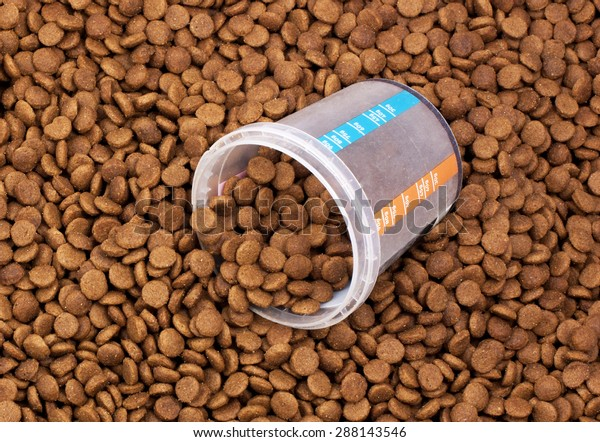 Dry brown pet food (dog or cat) with measure glass