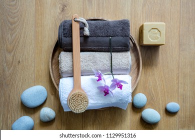 dry brushing, pampering towels, orchids and eco-friendly soap over zen stones on round wooden background for chic wellbeing, shower, bath or fresh massage, above view still life