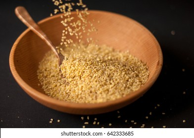 Dry bulgur wheat in brown wooden bowl isolated on dark wood.