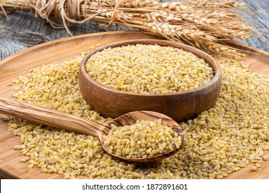 Dry bulgur wheat grains on wooden background. Vegetarian cuisine - dry bulgur for cooking.Wheat grains that have been steamed, dried and crushed; a staple of Middle Eastern cooking