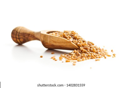Dry bulgur wheat grains in wooden scoop isolated on white background.