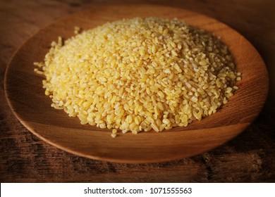 Dry bulgur wheat in wooden bowl isolated Spilled bulgur