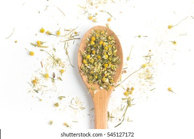 Dry Camomile Tea into a spoon isolated on white background