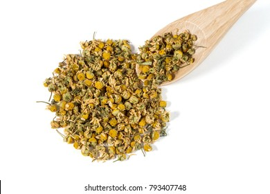 Dry Camomile Tea in a spoon on white background.
