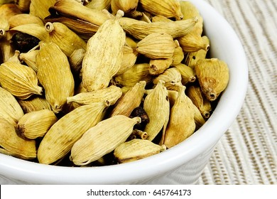 dry cardamom seeds - herb (Elettaria cardamomum) isolated on the white background
