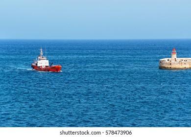 Dry cargo carrier at Breakwater at Fort Ricasoli of Kalkara at Grand Harbor in Valletta, Malta