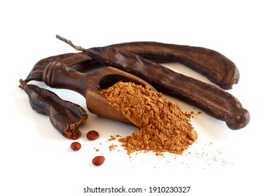 Dry carob powder in a scoop and pods close up isolated on white