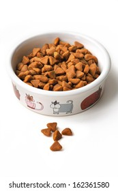 Dry cat food in a ceramic bowl on white background