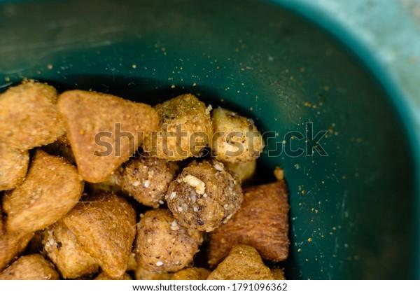 Dry Cat food in plastic bowl macro top view. Copyspace.