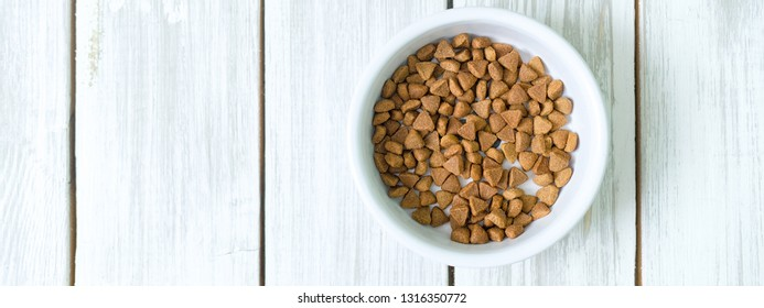 Dry cats food in a round bowl on white wooden floor overhead.