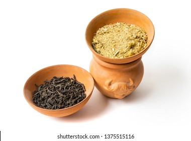 Dry chamomile and tea in pot on the white