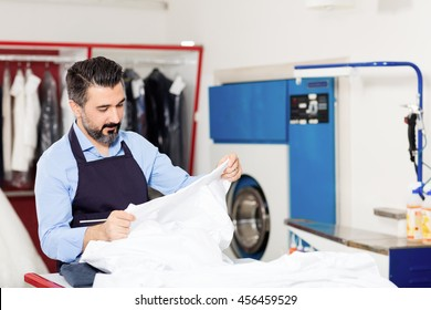 Dry cleaner working in shop.
