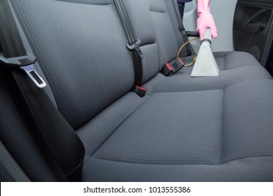 Dry cleaner's employee hand cleaning a car's gray textile seats with professionally extraction method. Early spring regular cleanup. Care about auto interior. Commercial cleaning company concept.