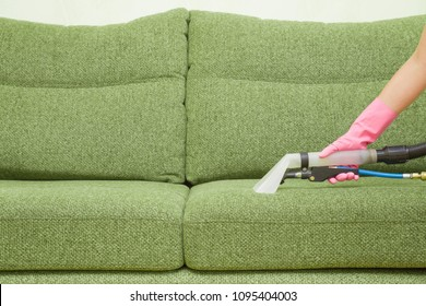 Dry cleaner's employee hand cleaning a green sofa with professionally extraction method. Textile upholstered furniture. Early spring regular cleanup. Commercial cleaning company. Service concept.