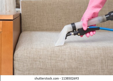 Dry cleaner's employee hand cleaning sofa with professionally extraction method. Textile upholstered furniture. Early spring regular cleanup. Commercial cleaning company. Service concept.