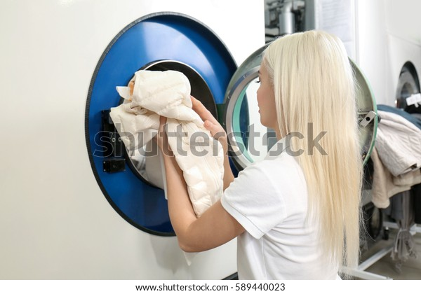 Dry cleaning business concept. Woman getting out clean clothes from washing machine